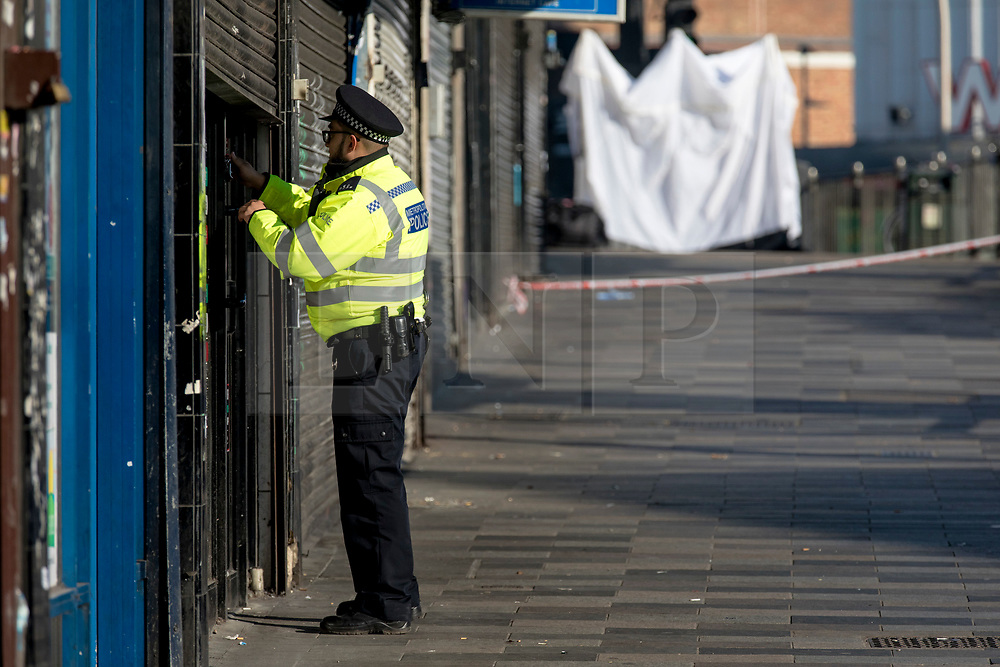 © Licensed to London News Pictures. 27/02/2019. London, UK. A police officer enters a shop near Ilford Station, where a 20-year-old man was fatally stabbed last night. A murder investigation has been launched. Photo credit: Rob Pinney/LNP