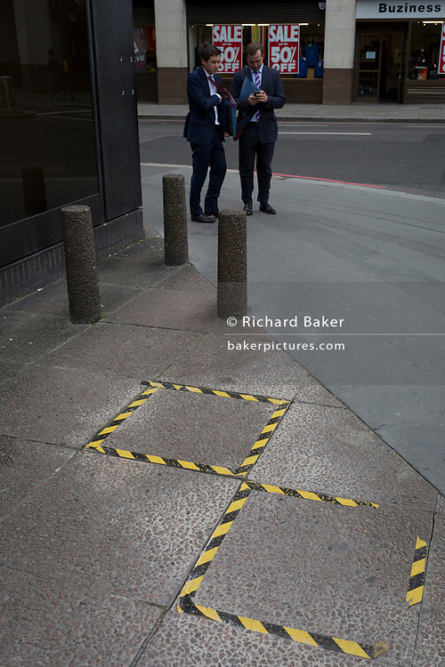 Two businessmen stand near wo pavement stones ringed with hazard tape, on 14th September 2017, in the City of London, England.