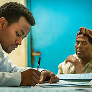 INDIVIDUAL(S) PHOTOGRAPHED: Dr. Amsaya Gebre (left) and Nebery Ayalew (right). LOCATION: Felege Hiwot Referral Hospital, Bahir Dar, Ethiopia. CAPTION: After performing a thorough examination, Dr. Amsaya Gebre writes a diagnosis for his patient.