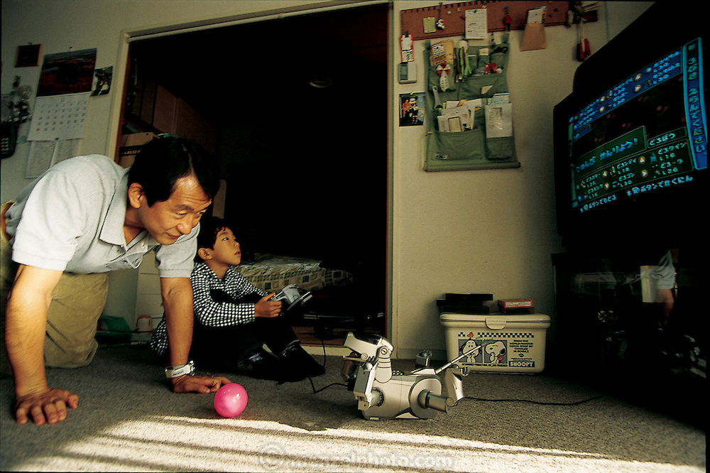 The novelty of owning Japan's first robot dog is not enough to keep Mitsuhiko Nozue's son Masahiko from switching his attention to a Pokemon video game. When abandoned by its owner, AIBO, Sony's new, limited-edition mechanical pet, plays with the ball by itself, delighting Mitsuhiko. The man runs for the 150-page manual that came with the robot pet when AIBO displays any new trick, sometimes leaving Mitsuhiko scratching his head; a puzzlement all too familiar from other encounters with digital gizmos. The latest word is that the Nozue family has named their AIBO Narubo. Yokohama, Japan . From the book Robo sapiens: Evolution of a New Species, page 226.