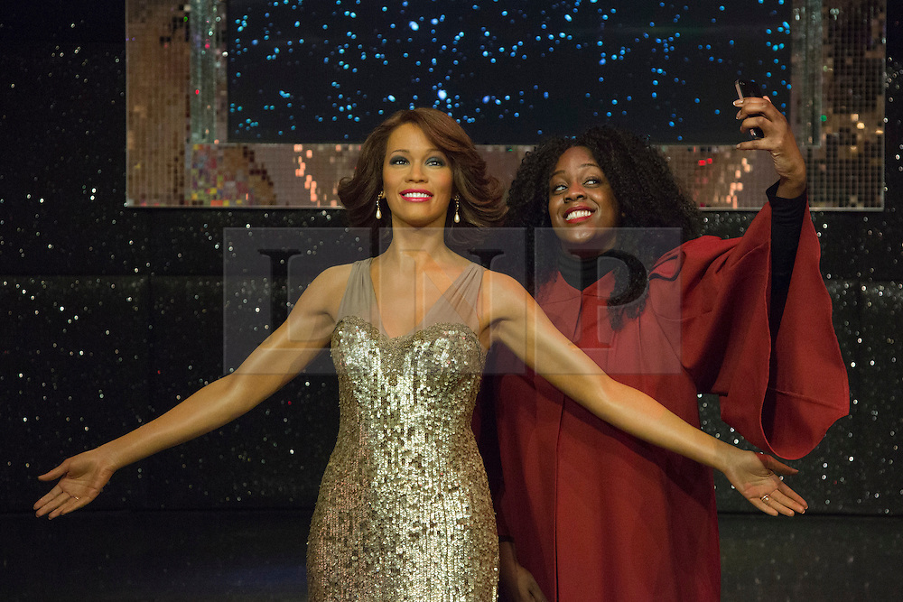 """© Licensed to London News Pictures. 21 October 2013. London, England. Pictured: gospel singer Simone Daley-Richards poses with the figure. The 30-strong """"London Gospel Factory Choir"""" today welcomed the wax figure of singer Whitney Houston at Madame Tussauds London, where it will be on display until the middle of December 2013. Photo credit: Bettina Strenske/LNP"""