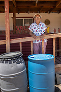 Stella Valdez, 81, is pictured in front of water barrels she uses for bathing and dish washing in Pretty Rock, near the White Rock Chapter in the remote Navajo Nation. Volunteers with Water Warriors filled up her water and donated a barrel so she had an extra stock.
