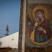 An Orthodox Icon is painted on a segment of the Israeli separation barrier. The Israeli West Bank barrier or wall is a separation barrier in the West Bank. Israel calls it a security barrier while Palestinians and many others call it a racial segregation or apartheid wall. At a total length of 708 kilometres (440 miles) upon completion, the border traced by the barrier is more than double the length of the Green Line, with 15% running along it or in Israel, while the remaining 85% cuts at times 18 kilometres (11 miles) deep into the West Bank, isolating about 9.4% of it, leaving an estimated 25,000 Palestinians isolated from the bulk of that territory.