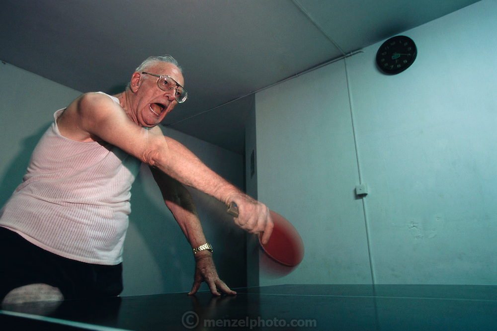 Colombo, Sri Lanka. Sir Arthur C. Clarke's daily dose of afternoon table tennis at the Otter Club. He is playing against one of his valets Lenin, and takes his game very seriously. Published in Stern Magazine, 28 December 2000, page 77. (He has post-polio syndrome) Best known for the book 2001: A Space Odyssey. MODEL RELEASED