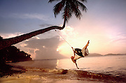 A young couple have fun on a tire swing hanging from a plam tree on the British Virgin Islands