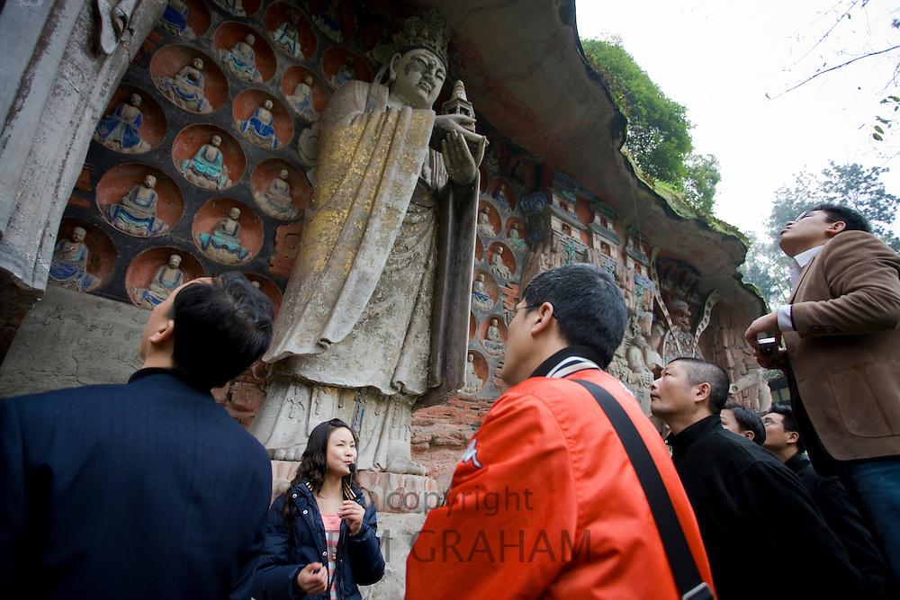 Tourists view Buddha statues Dazu rock carvings at Mount Baoding, Chongqing, China