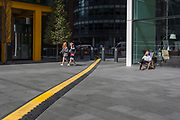 Two visitors to London walk through Leadenhall in the City of London, (aka The Square Mile) the capital's financial district, on 2nd September 2019, in London, England.