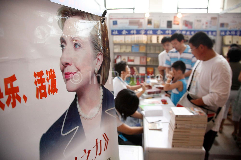 Visitors sort through books on offer beside a poster of U.S. Secretary of State Hillary Clinton at a book fair in Shanghai, China on 16 August 2009.  China may appeal a recent World Trade Organization (WTO) ruling that its limits on the sale of books, films and music from the US are unfair.