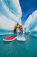 A couple on stand up paddle boards (SUP) kiss in an iceberg canyon on Bear Lake in Kenai Fjords National Park, Alaska.