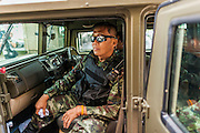 "20 MAY 2104 - BANGKOK, THAILAND:  A Thai army officer in a humvee type vehicle after the declaration of martial law. The Thai Army declared martial law throughout Thailand in response to growing political tensions between anti-government protests led by Suthep Thaugsuban and pro-government protests led by the ""Red Shirts"" who support ousted Prime Minister Yingluck Shinawatra. Despite the declaration of martial law, daily life went on in Bangkok in a normal fashion. There were small isolated protests against martial law, which some Thais called a coup, but there was no violence.  PHOTO BY JACK KURTZ"