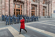 A woman wearing a face protective surgical mask walks in front of policemen outside the Armenian Government building in Yerevan on Monday, Dec 14, 2020. (VXP Photo/ Vudi Xhymshiti)
