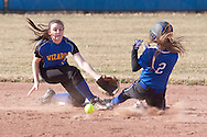 Middletown, New York - A Washingtonville infielder reaches for the ball as a Middletown player slides into second base in a varsity girls' softball game on April 9, 2014.