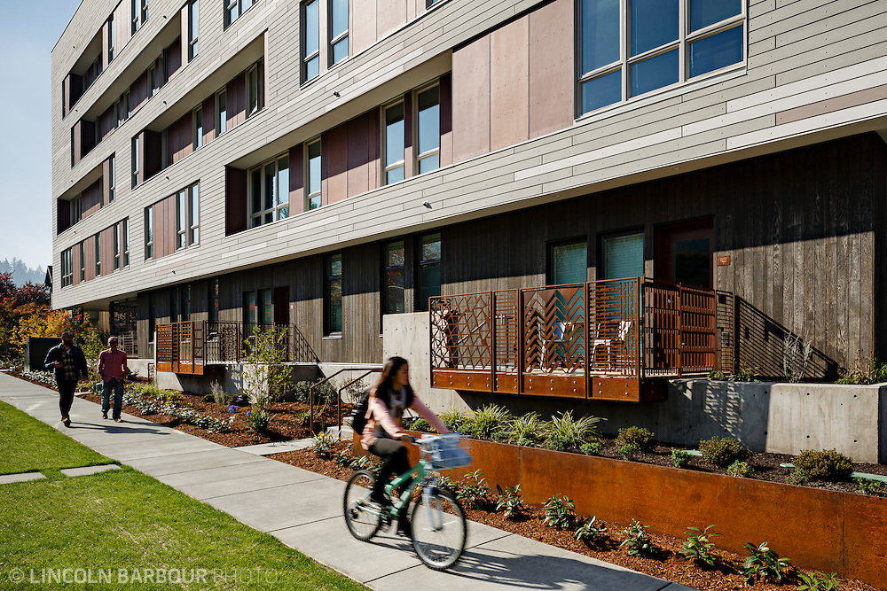 University House student housing apartment in Eugene, OR. Designed by Mahlum Architects. A female student rides her bike along the sidewalk with two male students walking behind her.