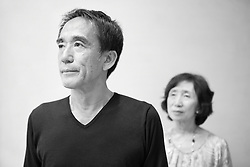 Black and white portrait photograph of middle age man in deep thoughts while wife anxiously watches him in background
