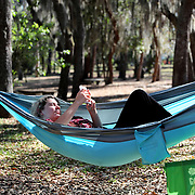 Student Brooke Barber relaxes alone in a hammock at Kraft Mead Gardens on Saturday, March 28, 2020 in Winter Park, Florida. Barber is on hiatus from school during the Coronavirus (COVID-19) threat. (Alex Menendez via AP)