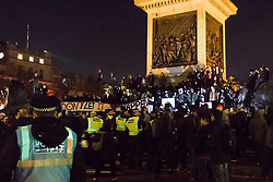 London, November 05 2017. Anti-capitalists gather in Trafalgar Square, London for the annual 'Million Mask March' which happens on November 5th every year, with many of the protesters donning 'V' For Vendetta Guy Fawkes masks. Past marches have turned violent with police horses shot by fireworks and police vehicles burned. PICTURED: Protesters on the base of Nelson's Column. © Paul Davey