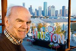 "Portrait of Artist David Adickes with sculpture of ""We Love Houston' with Houston, Texas skyline background."