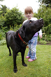 Young girl in the garden with pet dog,