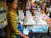 """13 FEBRUARY 2014 - BANGKOK, THAILAND: A person walks past a booth selling rice in Khlong Toei Market in Bangkok. The Thai government instituted a """"rice pledging scheme"""" after the election in 2011. The government agreed to buy farmers' rice crops at above market prices then planned to warehouse the rice and sell it on international markets when prices recovered. At the same time, India and Vietnam started to export large quantities of rice and the Thai government fell short of funds to pay for rice it had already purchased from farmers. Many farmers have not been paid for rice grown in 2013 and some of the rice in the Thai warehouses is allegedly rotting. Thailand has fallen from number 1 rice exporter in the world to number 3 and several government to government contracts the Thais signed with rice importing countries (like China) have been cancelled. Farmers, once key supporters of the government are now joining anti-government protests in Bangkok and occupying government ministries including the Ministry of Commerce.    PHOTO BY JACK KURTZ"""