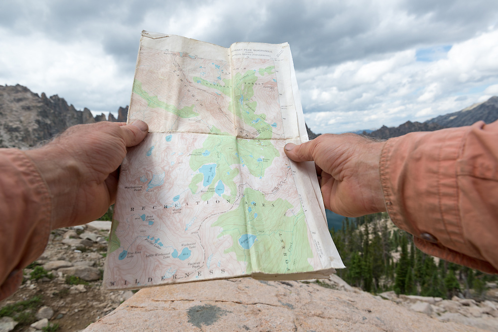 Hiker navigating by map in Idaho's Sawtooth Mountains.
