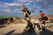 A man dressed as a giant skeleton dances with another man at Burning Man. Burning Man is a performance art festival known for art, drugs and sex. It takes place annually in the Black Rock Desert near Gerlach, Nevada, USA.
