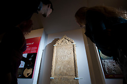 """© Licensed to London News Pictures 25/01/2016, Cirencester, UK. Collections officer James Harris (L) looks at a unique Roman tombstone, found in February 2015, here on display for the first time at Corinium Museum in Cirencester. The tombstone was found near skeletal remains thought to belong to the person named on its inscription, making the discovery unique. After being found during excavation works on a former site of a garage, archaeologists said they believed it marked the grave of a 27-year-old woman called Bodica. Other theories point to it possibly belonging to a couple - as skeletal remains of women were found nearby.<br /> The inscription reads """"To the shades of the dead, Bodicacia spouse lived 27 years"""". Photo Credit : Stephen Shepherd/LNP"""