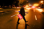"""07282016 - Philadelphia, Pennsylvania, USA: A delegate crosses Broad Street holding a sign from the convention reading, """"USA,"""" on the final day of the Democratic National Convention. (Jeremy Hogan/Polaris)"""