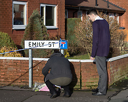 © Licensed to London News Pictures . 11/02/2014 . Blackburn , UK . Two boys leave flowers and a teddy bear at the scene . Police and forensic examiners on Emily Street in Blackburn at the scene where an eleven month old baby girl was mauled to death late last night (10th February 2014) . Photo credit : Joel Goodman/LNP