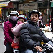 A family with a young girl travel on a scooter in the old quarter of Hanoi. Hanoi is the capital of Vietnam and the country's second largest city. Hanoi, Vietnam. 17th March 2012. Photo Tim Clayton