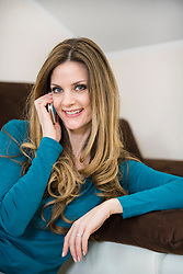 Smiling mature woman on couch with smartphone