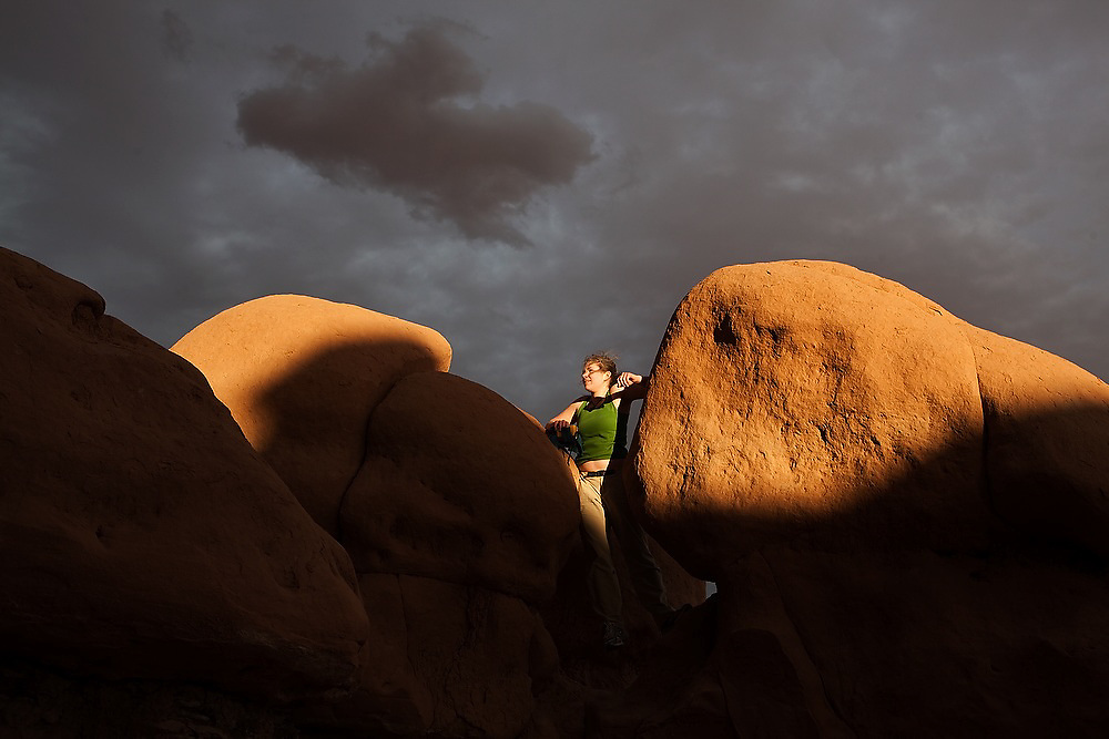 Jessica Stanley stands between two boulders, at sunset, during a geology field trip to Goblin Valley State Park, Utah.