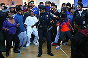 """Detective Denise """"Cookie"""" Bouldin dances with middle school students at South Shore K-8, June 2, 2016.  Bouldin works in the community outreach division of the Seattle Police Department and also runs Detective Cookie's Urban Youth Chess Club.  She teaches chess at Van Asselt and South Shore K-8 several time a week, including stopping in at lunch to play with the students."""