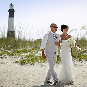 A father escorts his daughter along the beach to her wedding ceremony on Tybee Island as a lighthouse is seen in background. ©Travis Bell Photography