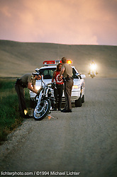 Walk the Line, Sturgis, SD, 1994<br /> <br /> Limited Edition Print from an edition of 50. Photo ©1994 Michael Lichter.<br /> <br /> Description: Where there are bikes, there's no shortage of police. Worse yet, regardless of why you're stopped, you could be illegally searched. That's what happened to me when my Harley was confiscated in 1979 for more than two years.  These are conservative times. Know your rights to protect your freedoms.<br /> <br /> Officer, please understand: I have the right to have an attorney present if you want to question me or conduct any search of my body or personal effects. I am not giving my consent to any type of search.<br /> <br /> If I am under arrest, I wish to invoke and exercise my Miranda Rights. I want to speak with an attorney now. I do not want my personal property impounded, nor do I consent to any impoundment. I request the opportunity to secure my personal effects. If I am not under arrest, please tell me immediately so that I may leave.<br /> <br /> From a popular wallet guide from Richard Lester