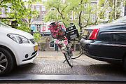 In Utrecht staat een met bloemen versierde fiets geparkeerd tussen twee auto's op de Oudegracht.<br /> <br /> In Utrecht a bike decorated with flowers is parked between two cars.