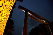 The entrance torii gate to of the controversial Yasukuni with a large display of yellow paper lanterns, each carrying the name of a fallen serviceman, at the Mitama matsuri or festival of remembrance for Japanese war dead Yasukuni shrine, Tokyo, Japan, Monday, July 16th 2007