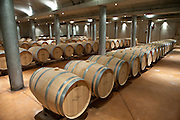 Oak wine barrels in cave at Chateau Beau-Sejour Becot at St Emilion in the Bordeaux wine region of France