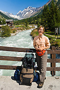 """Carol arrives with rolling luggage at a bridge over the Lonza River in Blatten, Loetschental, in the Valais canton of Switzerland, the Alps, Europe. UNESCO lists """"Swiss Alps Jungfrau-Aletsch"""" as a World Heritage Area (2001, 2007). For licensing options, please inquire."""