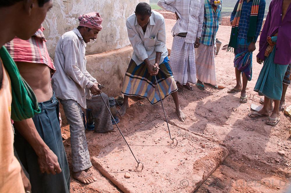 Men pulling the entrance cover of the brick making kiln to close it, Bangladesh.
