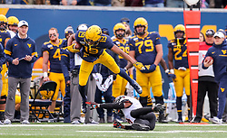 Nov 23, 2019; Morgantown, WV, USA; West Virginia Mountaineers wide receiver Ali Jennings (19) attempt to jump over Oklahoma State Cowboys cornerback A.J. Green (4) during the second quarter at Mountaineer Field at Milan Puskar Stadium. Mandatory Credit: Ben Queen-USA TODAY Sports