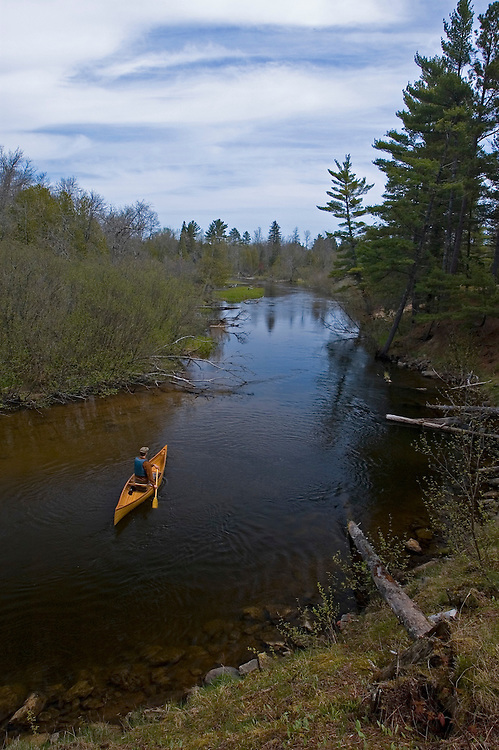 A solo canoeist paddles a cedar strip canoe on the AuTrain River in AuTrain, Michigan in spring.