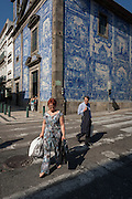 A quirky scene of a patterned wearing lady looked at strangely by a gentlemen, both crossing the Rua de Fernandes Tomas with Azulejo tiles on the exterior of Capela Das Almas, on 19th July, in Porto, Portugal. The Church's magnificent panels depict scenes from the lives of various saints, including the death of St Francis and the martyrdom of St Catherine. Eduardo Leite painted the tiles in a classic 18th-century style, though they actually date back only to the early 20th century. (Photo by Richard Baker / In Pictures via Getty Images)