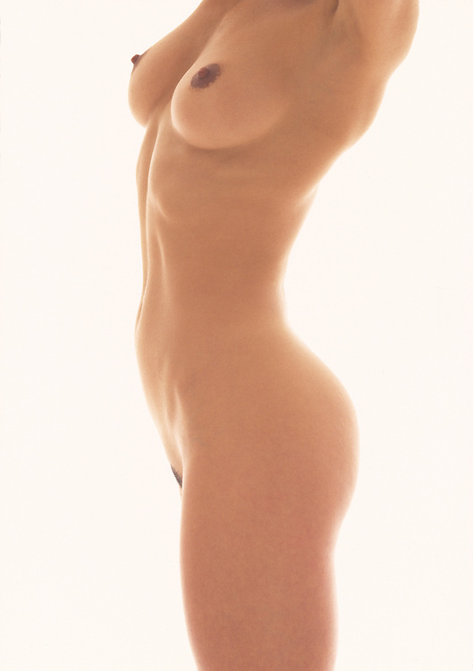 Nude woman's body photographed from shoulder to thigh with rich warm light and a white background