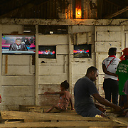 Watching TV at one of the public televisions that exists on the streets.