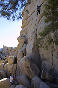 Adam belays for Doug D'Aluisio climbing a boulder at Joshua Tree National Monument, California. Christmas road trip from Napa, California to Sedona, Arizona and back. MODEL RELEASED..