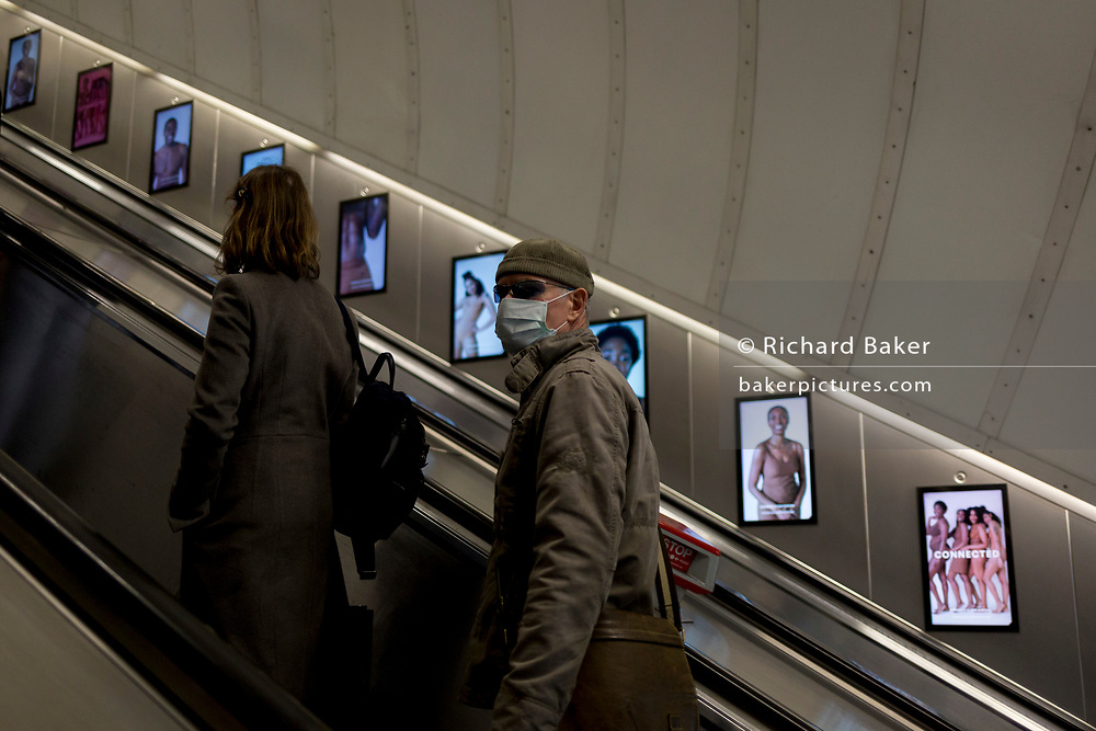 On the day that the UK government warns of 'draconian measures' to help control the spread of Coronavirus, a man wearing a surgical face mask obscuring his face and protecting from any Coronavirus contact, rides the up escalator in a London underground station, on 3rd March 2020, in London, England.