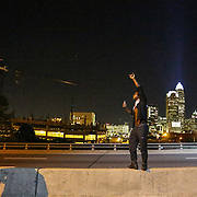 Charlotte, NC- September 23, 2016:  A protestor climbs up the median on interstate 277 to take a picture of the passing protest as they walk down the shutdown highway.  CREDIT: LOGAN R. CYRUS FOR THE NEW YORK TIMES