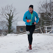 A runner makes her way in the snow on Hammer Knude.  Salomon Hammer Trail Winter Edition is a first on Bornholm and is one of the toughest routes in Denmark. The 4 runs consist of a 50 mile run, a marathon, a 1/2 marathon and 10k all run a on an approximate 25km route which includes 860 meter vertical rise on the North East coast of the Danish island Bornholm. The cut-off time for the 50mile run was 16 hours and more than a hundred runners made it to the finishing line. The last runner across the line after 50 miles  was in after 15:14:40