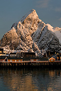 Early morning light on the mountains surrounding Reinefjord, in winter, with rorbuer (traditional fisherman's cottages) at Sakrisoy, viewed from from Olenilsoy, Moskenesoya, Lofoten Islands, Arctic Norway