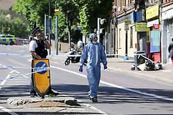 © Licensed to London News Pictures. 01/06/2019. London, UK. A forensic officer speaking and a police officer looking for evidence on Seven Sisters Road, near the junction of Vartry Road in Haringey, north London, where a man in his 30s was found suffering from a stab wound to his leg. Police were called by London Ambulance Service just after 3am on Saturday, 1 June 2019. The victims condition in unknown.  Photo credit: Dinendra Haria/LNP